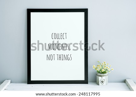 scandinavian or american style room interior with black frame - poster quote COLLECT MOMENTS, NOT THINGS and chamomile bouquet in diy concrete pot  - stock photo