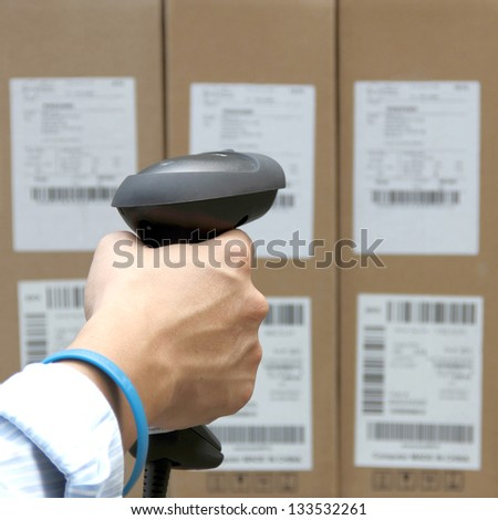 Scanning the label on the boxes with barcode scanner - stock photo