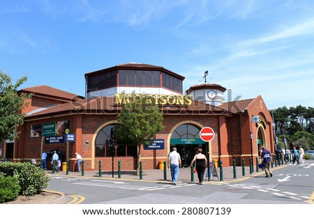 SCARBOROUGH, NORTH YORKSHIRE, ENGLAND - 15th of July 2013: People walking into the Morrisons supermarket to do their weekly shopping. This is one of the most popular supermarkets in England. - stock photo