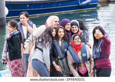 Scarborough, United Kingdom June 13, 2015: Group of women wearing life vests taking a selfie on their phone before going for a boat cruise.