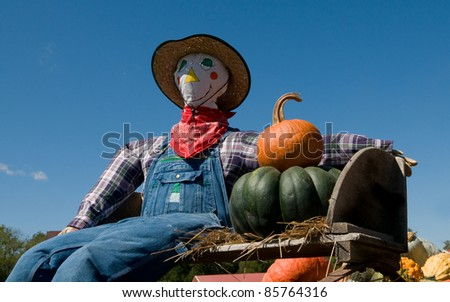 scarecrow and pumpkins in a wagon - stock photo