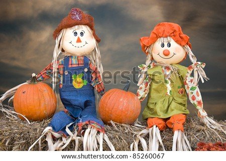 scarecrow couple with pumpkins on hay bales - stock photo