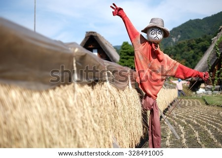 Scarecrow in a countryside landscape with golden rice fields - stock photo