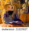 Scarecrow sitting on a pumpkin - stock photo