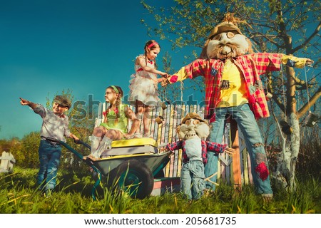Scarecrows and children in the garden  - stock photo