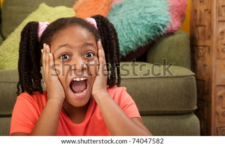 Scared African American girl in a room - stock photo