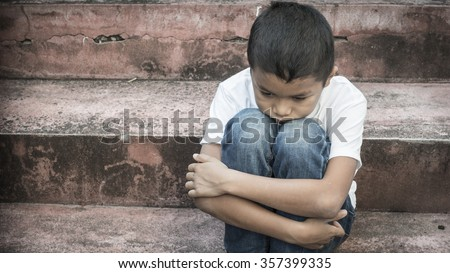 scared and alone, young homeless Asian child who is at high risk of being bullied, trafficked and abused