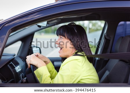 Scared and surprised woman with big eyes holds the steering wheel with both hands shouts driving the car - outdoors