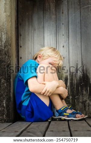 Scared boy hiding in old building - stock photo
