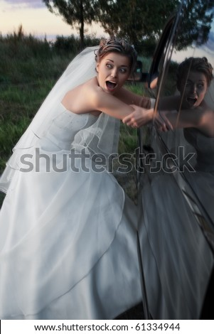 Scared bride in white dress being kidnapped into a black car in the evening
