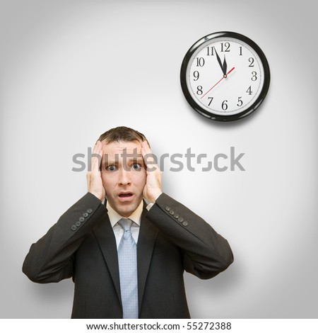 scared businessman and clock behind