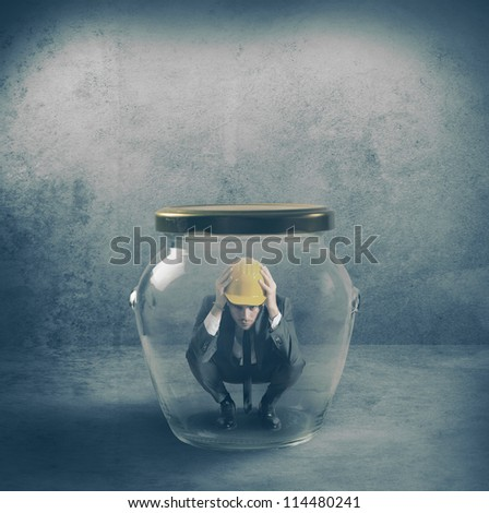 Scared businessman in a jar - stock photo