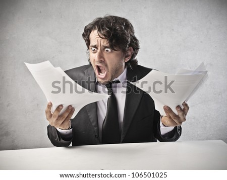 Scared businessman looking at some documents - stock photo