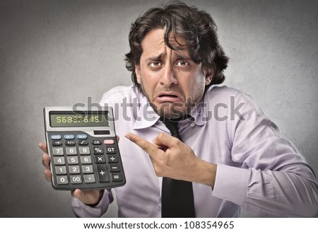 Scared businessman showing a calculator - stock photo