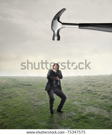 Scared businessman with threatening hammer over his head - stock photo