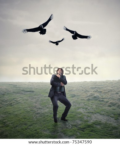 Scared businessman with threatening hawks flying over him