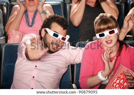 Scared Caucasian couple with 3D glasses in theater - stock photo