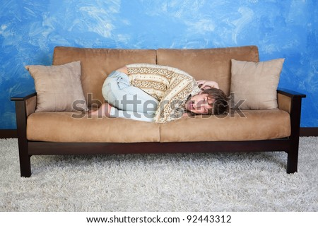 Scared Caucasian teen curled up on sofa - stock photo