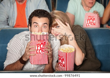 Scared couple hiding behind popcorn bags - stock photo