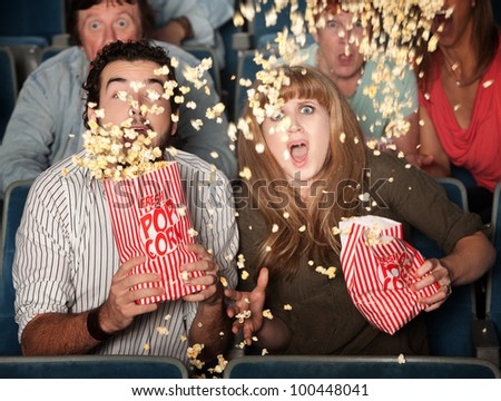 Scared couple jump in their seats with spilled popcorn - stock photo