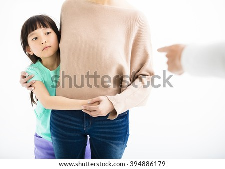 Scared daughter hiding behind mother from angry father - stock photo