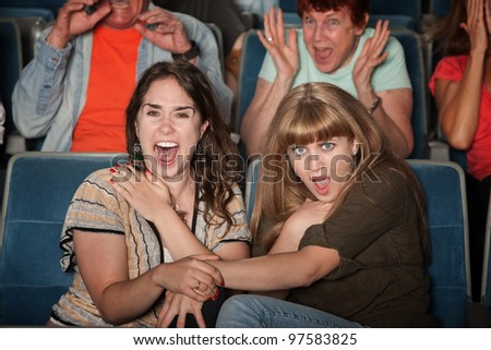 Scared friends in theater holding hands and screaming
