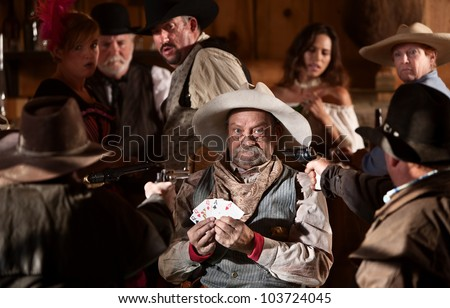 Scared gambler with winning cards and angry players - stock photo