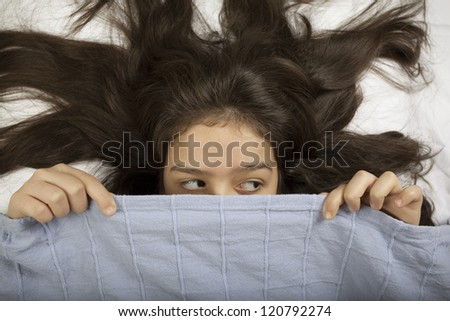 Scared girl hiding in bed