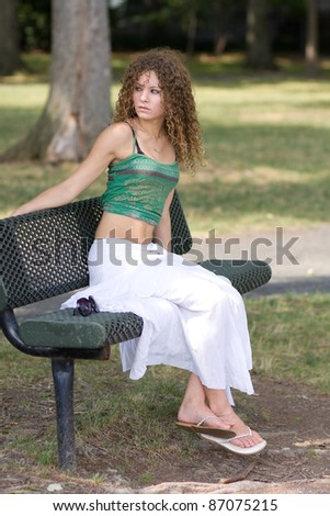 Scared girl on park bench - stock photo