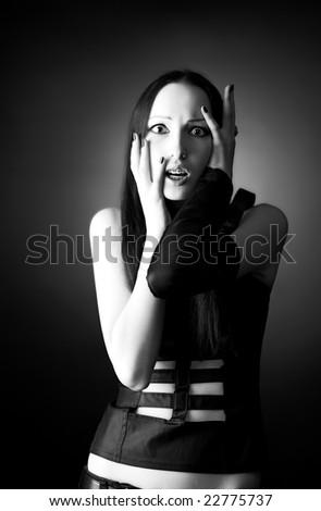 Scared goth woman portrait. On dark background. - stock photo