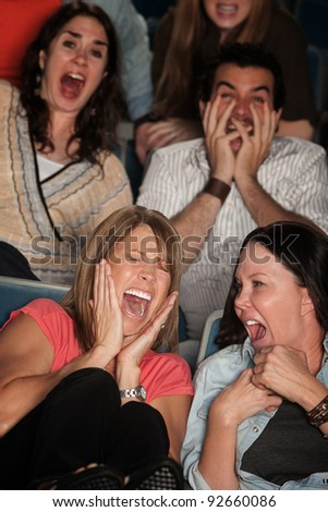 Scared group of spectators in theater seats scream in fear - stock photo