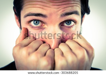 Scared hipster with hands to face on vignette background