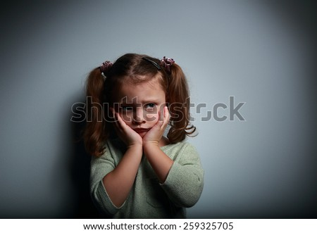 Scared kid girl with hands near face looking with horror on dark background with empty space for text - stock photo