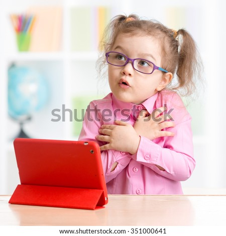 Scared kid with tablet PC in spectacles - stock photo