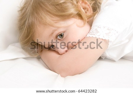 Scared little blond girl in the bed close-up - stock photo