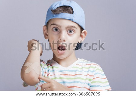 Scared little boy showing band aid in hand - stock photo