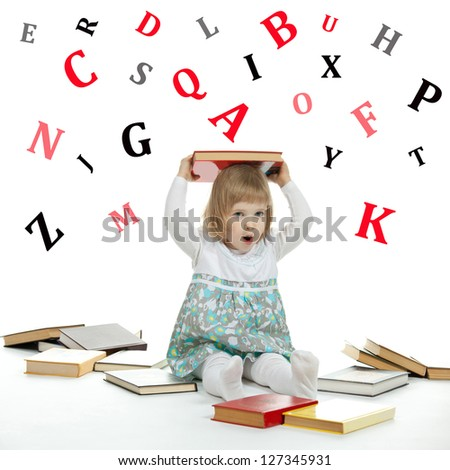 Scared little child sitting on the floor surrounded by books and alphabetical letters - stock photo
