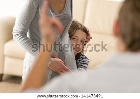 Scared little girl hiding behind mother from violent father - stock photo