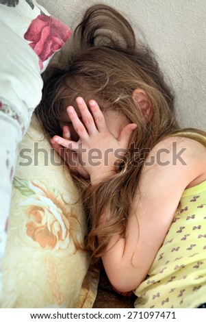 Scared Little Girl on the Bed in the Domestic Room - stock photo