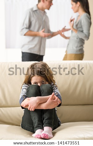 Scared little girl sitting on the couch listening to parents argument - stock photo