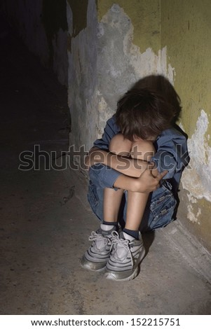 Scared lonely little boy in a dark cellar - stock photo