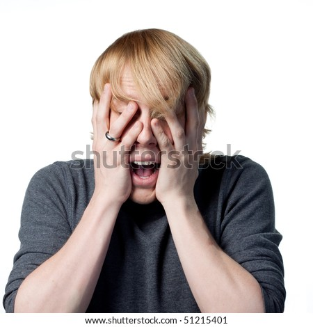 Scared man hiding behind his hands from something unseen - stock photo