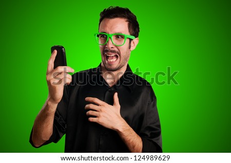 scared man holding phone on green background