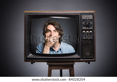 Scared man in old TV screen. - stock photo