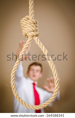 Scared man is suit with hanging noose - stock photo