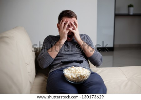 Scared man watching tv hiding his eyes - stock photo