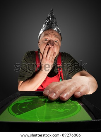 Scared man wearing a foil hat and watching old radar monitor with ufo - stock photo