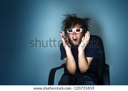 scared man with 3d anaglyph glasses in cinema chair - stock photo