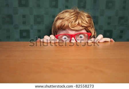 Scared nerd hiding behind a desk - stock photo