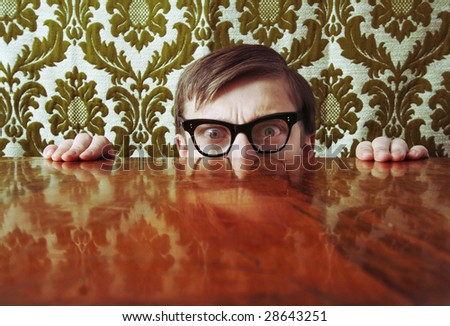 Scared nerd hiding behind a desk, similar available in my portfolio - stock photo